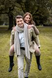Young couple in love piggyback at a park Stock Photos