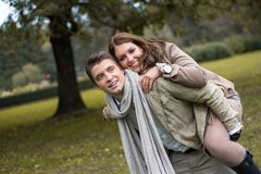 Young couple in love piggyback at a park Royalty Free Stock Photography