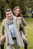 Young couple in love piggyback at a park Stock Images