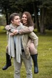 Young couple in love piggyback at a park Royalty Free Stock Images
