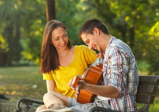 Young couple in love playing acoustic guitar Royalty Free Stock Photo