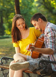 Young couple in love playing acoustic guitar Royalty Free Stock Photos