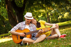 Young couple in love playing acoustic guitar. In the park Stock Photography