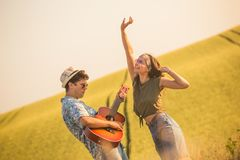 Romantic hipster couple singing their favorite song in nature. Love and summertime concept. Young couple in love playing guitar and dancing in the field Royalty Free Stock Photo