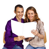 Young couple in love reading together a brochure Stock Image