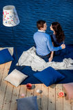 Young couple in love relaxing on terrace near water Royalty Free Stock Photos