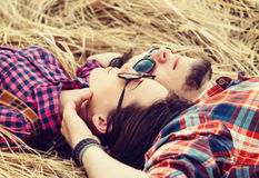 Young couple in love rests. Hipster young couple in love rests and dream on dry grass Royalty Free Stock Photos
