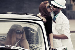 Young couple in love at the retro car. Young couple and jealous girl in a retro car Stock Photos