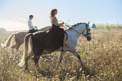 Young couple in love riding a horse royalty free stock image