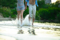 Young couple in love running through the water holding hands Stock Images