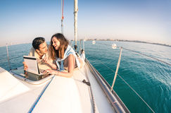 Young couple in love on sail boat having fun with tablet. Happy luxury lifestyle on yacht sailboat - Technology interaction with satellite wifi connection Stock Photography
