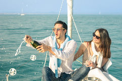 Young couple in love on sailing boat cheering with champagne