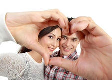 Young couple in love showing heart with fingers. Happy young couple in love showing heart with fingers isolated over white background Stock Image