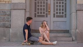 Young couple in love sit on threshold steps on Nevsky prospect and talk in slo-mo. Young sport looking man treats his smiling and splendid girlfriend with an stock footage