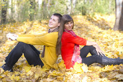 Young couple in love sitting back to each other. Royalty Free Stock Image