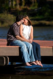 Young Couple In Love Sitting Barefoot On Dock. A young couple in love share a warm, intimate moment while sitting barefoot on a dock by a lake Stock Image