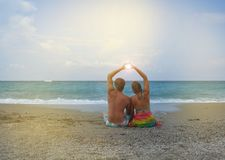 Young couple in love sitting on the beach and folded his hands in the shape of a heart, through the sun shines stock photo