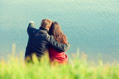 Young couple in love sitting on the seashore royalty free stock photo