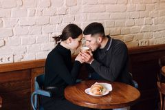 Young couple in love sitting in a cafe, drinking morning coffe royalty free stock photos