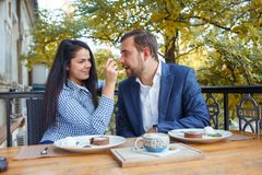 Young couple in love is sitting in cafe and woman is feeding cake her man. Stock Images