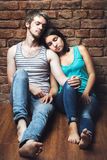 Young couple in love sitting on the floor Royalty Free Stock Photos