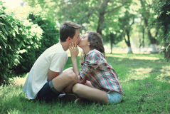 Young couple in love sitting on grass and kissing Royalty Free Stock Images