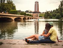 Young couple in love sitting near lake in park landscape