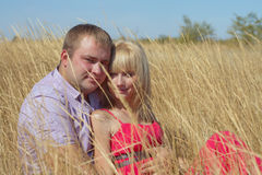 Young couple in love sitting in an open field in the arms Royalty Free Stock Images