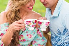 Young couple in love sitting on a picnic plaid in a park, drinking tea and enjoying their day out in nature Stock Image