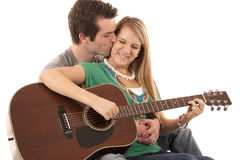 Young couple in love sitting playing guitar kissing Royalty Free Stock Photography