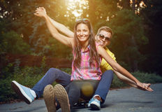 Young couple in love sitting on a skateboard outdoors Royalty Free Stock Images