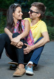 Young couple in love sitting on a skateboard outdoors Stock Photos