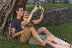 Young Couple in Love sitting under a tree in a castle stock images