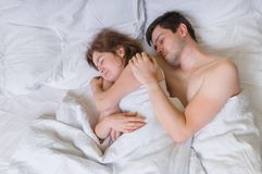 Young couple in love sleep together in bed Stock Images