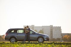 Young couple in love, slim attractive woman with long ponytail and handsome man standing together at silver car in green field on stock photo