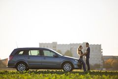 Young couple in love, slim attractive woman with long ponytail and handsome man standing together at silver car in green field on stock images