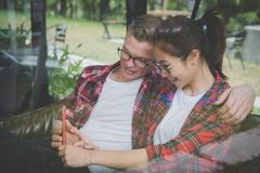 Young couple in love smile & look at smart phone. caucasian man royalty free stock photography