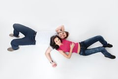 Young couple in love smiling at camera. Young couple laying on floor smiling at the camera Royalty Free Stock Images