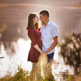 Young couple in love standing and kissing at river Royalty Free Stock Image