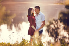 Young couple in love standing and kissing at river Stock Photos