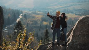 Young couple in love standing on the rocks and taking a selfie portrait. Man and woman visiting famous tourist stock footage