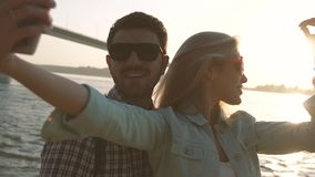 Young couple in love taking selfie together after wonderful day on beach stock video footage