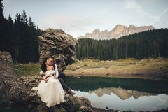 Stylish couple of newlyweds against the backdrop of the mountain. Young couple in love travelling, beautiful views of italian dolomites and mountain lake stock photo