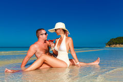 Young couple in love at the tropical beach and enjoying cocktail Stock Image
