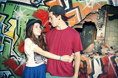 Young couple in love in an urban place with graffiti Royalty Free Stock Image
