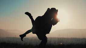 Young couple in love on vacations enjoying mountains. Attractive man is carrying girlfriend on his shoulders and whirls. Her. Having fun stock video