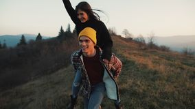 Young couple in love on vacations enjoying mountains. Attractive man is carrying girlfriend on his shoulders and whirls. Her. Having fun stock video footage