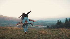 Young couple in love on vacations enjoying mountains. Attractive man is carrying girlfriend on his shoulders and whirls. Her. Having fun stock footage