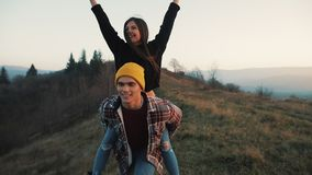 Young couple in love on vacations enjoying mountains. Attractive man is carrying girlfriend on his shoulders and whirls