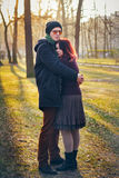 Young couple in love walking in the autumn park. Holding hands looking in the sunset Royalty Free Stock Images